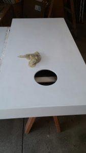 Clean the cornhole board with tack cloth